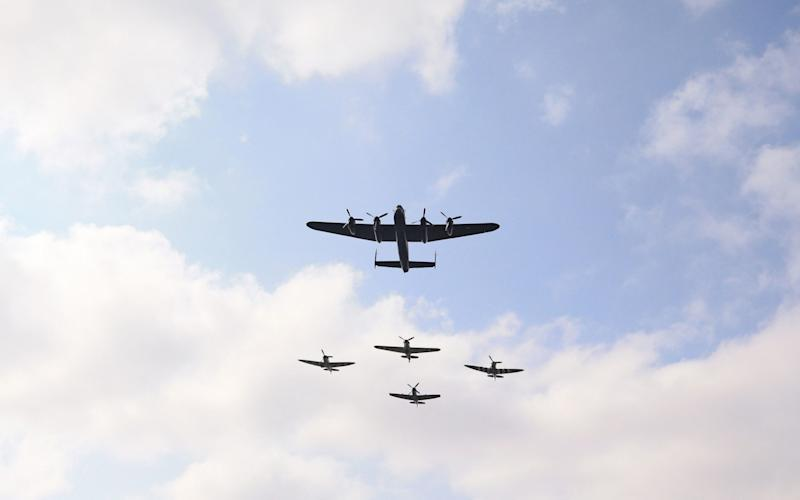 Three Spitfires, a Hurricane and a Lancaster bomber fly over the national service - Peter Byrne/PA