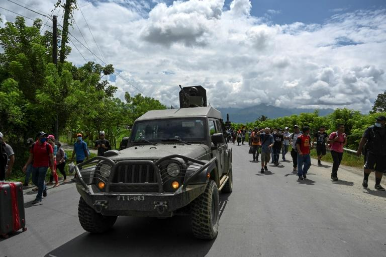 Honduran migrants, part of a caravan heading to the US, walk alongside an army truck in Entre Rios, Guatemala, after crossing the border on October 1, 2020