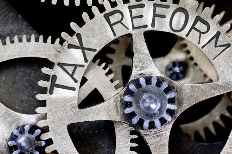 """Clockwork gears in metal, with the words """"Tax Reform"""" engraved on the side."""