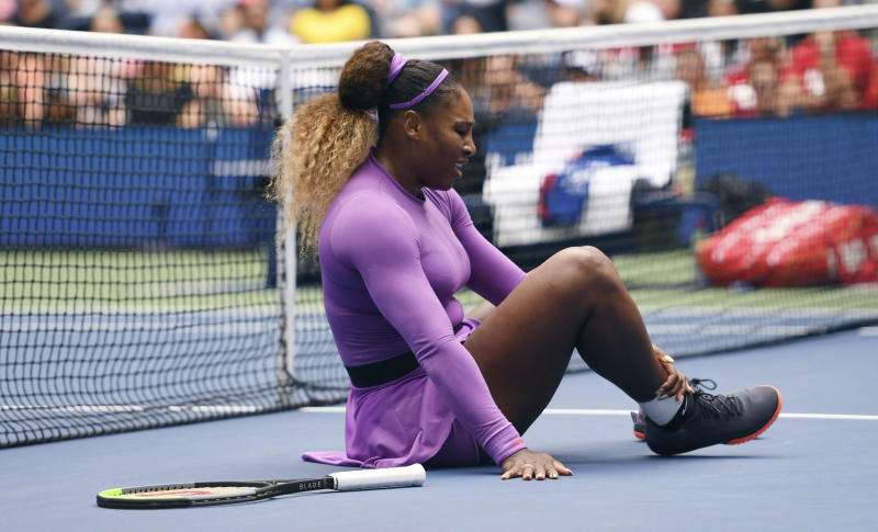 Serena Williams, of the United States, grabs her ankle after falling while chasing a return against Petra Martic, of Croatia, during round four of the US Open tennis championships Sunday, Sept. 1, 2019, in New York. (AP Photo/Sarah Stier)