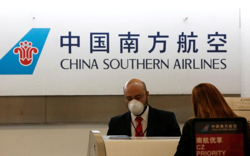 FILE PHOTO: A China Southern Airlines employee wears a surgical mask as a preventive measure in light of the coronavirus outbreak in China, while he attends a customer behind the counter at Benito Juarez international airport in Mexico City