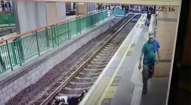 Horror moment thug pushes unsuspecting woman onto railway tracks