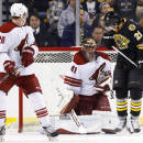 Arizona Coyotes goalie Mike Smith makes a save with Boston Bruins' Loui Eriksson (21) in front and defenseman Michael Stone (26) looking on during the first period of an NHL hockey game in Boston Saturday, Feb. 28, 2015. (AP Photo/Winslow Townson)