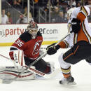 New Jersey Devils goaltender Cory Schneider, left, deflects a shot by Anaheim Ducks' Ryan Getzlaf during the first period of an NHL hockey game Sunday, March 29, 2015, in Newark, N.J. (AP Photo/Bill Kostroun)