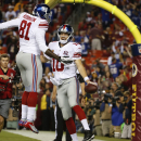New York Giants quarterback Eli Manning (10) celebrates his touchdown with teammate Adrien Robinson (81) during the second half of an NFL football game against the Washington Redskins in Landover, Md., Thursday, Sept. 25, 2014. (AP Photo/Alex Brandon)