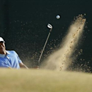 Tiger Woods of the U.S. hits out of a bunker on the 11th hole during a practice round ahead of the British Open golf championship at Muirfield in Scotland July 17, 2013.   REUTERS/Brian Snyder