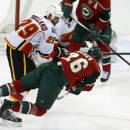 Minnesota Wild's Thomas Vanek, right, of Austria, trips over Calgary Flames' Deryk Engelland after making a pass in the first period of an NHL hockey game, Friday, March 27, 2015, in St. Paul, Minn. (AP Photo/Jim Mone)