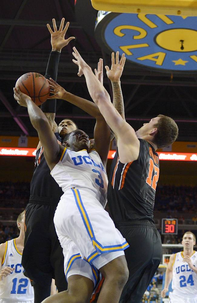 UCLA guard Jordan Adams, center, puts up a shot as Oregon State forward Eric Moreland, left, and center Angus Brandt defend during the first half of an NCAA college basketball game, Sunday, March 2, 2014, in Los Angeles