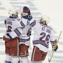 New York Rangers left wing Carl Hagelin (62), of Sweden, and right wing Martin St. Louis (26) congratulate center Derick Brassard (16) after his third goal, during the third period of Game 6 of the Eastern Conference finals against the Tampa Bay Lightning, in the NHL hockey Stanley Cup playoffs, Tuesday, May 26, 2015, in Tampa, Fla. The Rangers won 7-3. (AP Photo/Phelan M. Ebenhack)