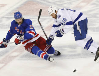 New York Rangers defenseman Dan Boyle (22) and Tampa Bay Lightning left wing Brenden Morrow (10) lose their footing as they battle for the puck during the third period of Game 5 of the Eastern Conference final during the NHL hockey Stanley Cup playoffs, Sunday, May 24, 2015, in New York. (AP Photo/Kathy Willens)