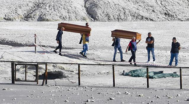 The coffins of three dead people are carried away out of the volcanic zone. Source AAP