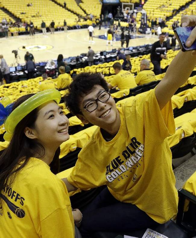 Wenli Xu, left, and Ziang Wang take a photo of themselves before an opening-round NBA basketball playoff series between the Indiana Pacers and the Atlanta Hawks, Saturday, April 19, 2014, in Indianapolis