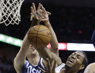 San Antonio Spurs' Kawhi Leonard (2) and Dallas Mavericks' Dirk Nowitzki, left, of Germany, fight for a rebound during the first half of Game 2 of the opening-round NBA basketball playoff series on Wednesday, April 23, 2014, in San Antonio. (AP Photo/Eric Gay)