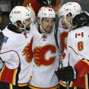 Calgary Flames' Josh Jooris, center, is congratulated by teammates after his goal off Minnesota Wild goalie Devan Dubnyk in the first period of an NHL hockey game, Friday, March 27, 2015, in St. Paul, Minn. (AP Photo/Jim Mone)
