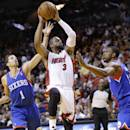 Miami Heat guard Dwyane Wade (3) goes up to shoot against Philadelphia 76ers guard Michael Carter-Williams (1) and forward Thaddeus Young, right, during the first half of an NBA basketball game on Wednesday, April 16, 2014, in Miami. (AP Photo/Wilfredo Lee)