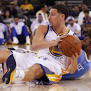 Golden State Warriors' Klay Thompson looks to pass next to Denver Nuggets' Alonzo Gee during the second half of a preseason NBA basketball game, Friday, Oct. 24, 2014, in Oakland, Calif. The Warriors won 119-112. (AP Photo/George Nikitin)
