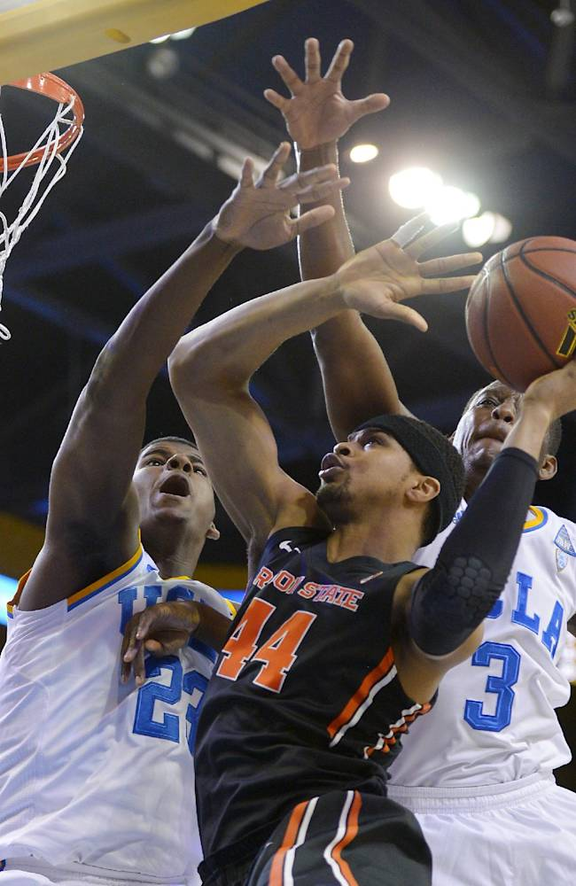 Oregon State forward Devon Collier, center, goes up for a shot as UCLA center Tony Parker, left, and guard Jordan Adams defend during the first half of an NCAA college basketball game, Sunday, March 2, 2014, in Los Angeles