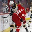 Boston Bruins' Reilly Smith (18) battles with Carolina Hurricanes' John-Michael Liles (26) during the first period of an NHL hockey game, Sunday, March 29, 2015, in Raleigh, N.C. (AP Photo/Karl B DeBlaker)