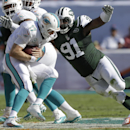 New York Jets defensive end Sheldon Richardson (91) sacks Miami Dolphins quarterback Ryan Tannehill (17) during the first half of an NFL football game, Sunday, Dec. 28, 2014, in Miami Gardens, Fla. (AP Photo/Wilfredo Lee)