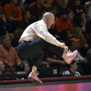 Virginia Tech's head coach Buzz Williams jumps after his team scored a 3-point basket against Virginia during the first half of an NCAA college basketball game Sunday, Jan. 25, 2015, in Blacksburg, Va. (AP Photo/Don Petersen)