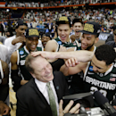 Michigan State head coach Tom Izzo, center front, celebrates with his team after the regional final against Louisville in the NCAA men's college basketball tournament Sunday, March 29, 2015, in Syracuse, N.Y. Michigan State won the game 76-70. (AP Photo/Seth Wenig)