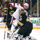 Arizona Coyotes' Lucas Lessio runs into Boston Bruins goalie Tuukka Rask during the first period of an NHL hockey game in Boston Saturday, Feb. 28, 2015. (AP Photo/Winslow Townson)
