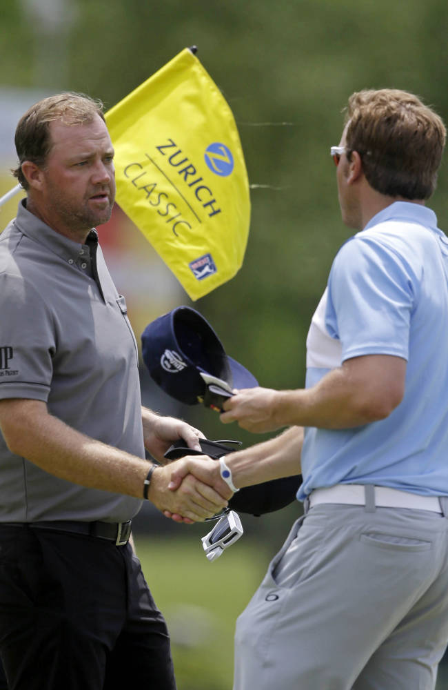 Peter Hanson, left, of Sweden, shakes hands with Ricky Barnes on the ninth green as they finished the opening round of the Zurich Classic golf tournament at TPC Louisiana in Avondale, La., Thursday, April 24, 2014