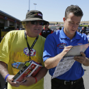 A.J. Allmendinger, right, signs autographs in the garage area before practice for the NASCAR Sprint Cup Series auto race Friday, June 26, 2015, in Sonoma, Calif. Allmendinger earned a spot in the championship race with a win on a road course. He'll try to do it again this year at Sonoma Raceway, the first of two road courses on the NASCAR schedule. (AP Photo/Eric Risberg)