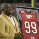 Former Tampa Bay Buccaneers player Warren Sapp smiles after being inducted in the Ring of Honor ceremony during halftime in an NFL football game between the Tampa Bay Buccaneers and the Miami Dolphins in Tampa, Fla., Monday, Nov. 11, 2013.(AP Photo/Phelan M. Ebenhack)