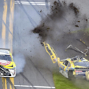 Regan Smith (7) lands on the infield grass after flipping on the front stretch after being involved in a multi-car accident, as Jeff Green (10) drives past, during a NASCAR Xfinity series auto race at Daytona International Speedway, Saturday, Feb. 21, 2015, in Daytona Beach, Fla.(AP Photo/Phelan M. Ebenhack)