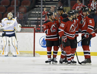 New Jersey Devils' Adam Larsson (5) celebrates his goal with teammates as Nashville Predators goaltender Carter Hutton, left, looks on during the first period of an NHL hockey game Tuesday, March 3, 2015, in Newark, N.J. (AP Photo/Bill Kostroun)