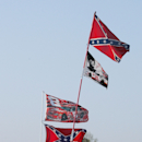 Confederate stars and bars fly on flag poles attached to campers with the driver flags of Kevin Harvick (29), Dale Earnhardt Jr. (8) and Mark Martin (6) at Atlanta Motor Speedway in Hampton, Ga., Friday, March 18, 2005. (AP Photo/Ric Feld)