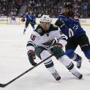 Minnesota Wild defenseman Matt Dumba, left, pursues a loose puck with Colorado Avalanche center Maxime Talbot in the first period of an NHL hockey game Saturday, Feb. 28, 2015, in Denver. (AP Photo/David Zalubowski)