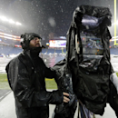 A television cameraman checks his equipment in the rain before an AFC divisional NFL playoff football game between the Indianapolis Colts and New England Patriots in Foxborough, Mass., Saturday, Jan. 11, 2014. (AP Photo/Michael Dwyer)
