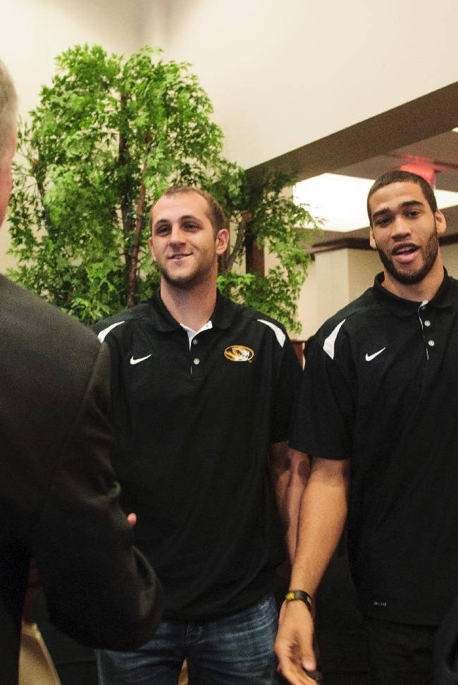 New Missouri men's basketball coach Kim Anderson, left, greets players Ryan Rosburg, center left, and Keanau Post, after Anderson introduced at an NCAA college basketball news conference in the Reynolds Alumni Center on Tuesday, April 29, 2014, in Columbia, Mo