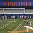 The Virginia football squad runs a play during spring NCAA college football practice at the school's indoor facility in Charlottesville, Va. (AP)
