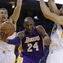 Los Angeles Lakers' Kobe Bryant (24) drives the ball between Golden State Warriors' Klay Thompson, left, and Andrew Bogut during the second half of an NBA basketball game Saturday, Nov. 1, 2014, in Oakland, Calif. (AP Photo/Ben Margot)