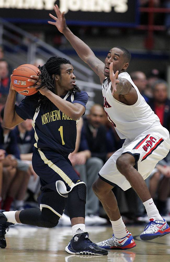 Northern Arizona's Aaseem Dixon (1) looks to pass against Arizona's Rondae Hollis-Jefferson during the first half of an NCAA college basketball game Monday, Dec. 23, 2013, in Tucson, Ariz