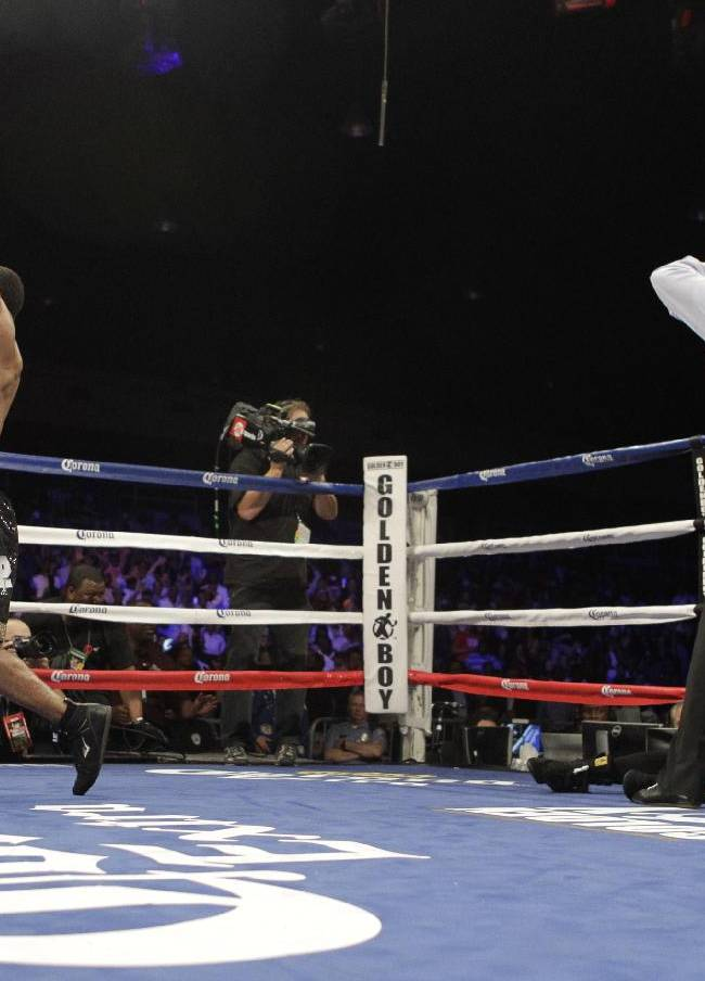 Shawn Porter, left, defeats Paulie Malignaggi, bottom right, during a TKO in the fourth round of their IBF Welterweight Championship boxing match, Saturday, April 19, 2014, in Washington