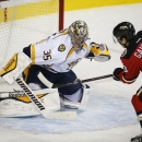 Nashville Predators goalie Pekka Rinne, left, from Finland, stops a shot form Calgary Flames' Johnny Gaudreau during the first period of an NHL hockey game Friday, Oct. 31, 2014, in Calgary, Alberta. (AP Photo/The Canadian Press, Jeff McIntosh)