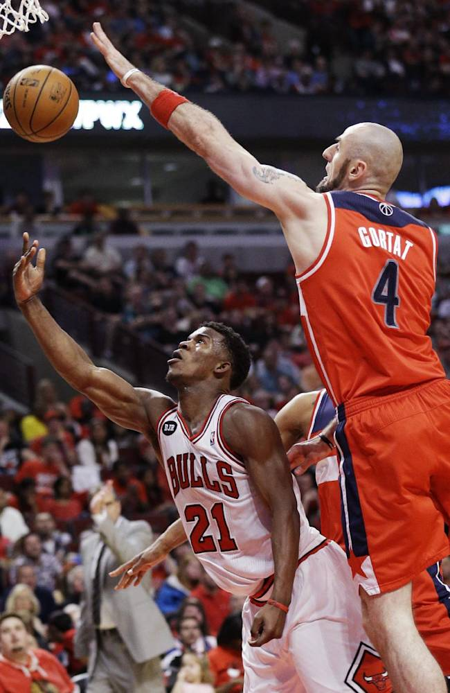 Chicago Bulls guard Jimmy Butler (21) shoots against Washington Wizards center Marcin Gortat (4) during the second half in Game 1 of an opening-round NBA basketball playoff series in Chicago, Sunday, April 20, 2014. The Wizards won 102-93