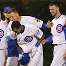 Chicago Cubs' Anthony Rizzo, top and Kris Bryant, right, celebrate with Addison Russell, after Russell's game winning double off Washington Nationals relief pitcher Matt Grace during the ninth inning of a baseball game Tuesday, May 26, 2015, in Chicago. Jonathan Herrera scored on the play giving the Cubs a 3-2 win. (AP Photo/Charles Rex Arbogast)