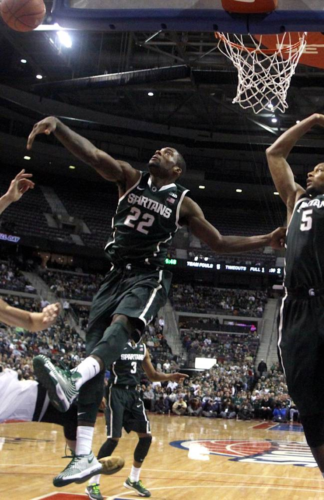 Michigan State's Branden Dawson (22) blocks a shot by Oakland's Travis Bader (3) as Michigan State's Adreian Payne (5) watches during the second half of an NCAA college basketball game, Saturday, Dec. 14, 2013, in Auburn Hills, Mich. Michigan State won 67-63