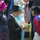 FILE - In this June 19, 2014 file photo, Britain's Queen Elizabeth II, second right, talks to her jockey Ryan Moore, right, in the parade ring ahead of the Gold Cup race in which her horse Estimate finished second behind Leading Light, on the third day of the Royal Ascot horse racing meeting, which is traditionally known as Ladies Day, at Ascot, England. British horse racing authorities have launched an online campaign to explain various aspects of horse racing, in an effort to broaden the appeal of the sport and make it less elitist. (AP Photo/Alastair Grant, File)