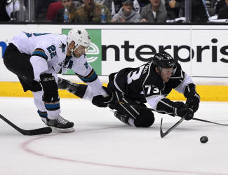 Los Angeles Kings center Tyler Toffoli, right, trips as he shoots the puck under pressure from San Jose Sharks defenseman Dan Boyle during the second period in Game 3 of an NHL hockey first-round playoff series , Tuesday, April 22, 2014, in Los Angeles. (AP Photo/Mark J. Terrill)