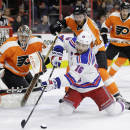 New York Rangers' Derick Brassard (16) tries to pass the puck as, from left to right, Philadelphia Flyers' Steve Mason, Sean Couturier, Michael Del Zotto and Braydon Coburn look on during the first period of an NHL hockey game, Saturday, Feb. 28, 2015, in Philadelphia. (AP Photo/Matt Slocum)