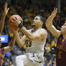 Wichita State guard Fred VanVleet goes to the basket against Loyola of Chicago guard Earl Peterson, left, and guard Joe Crisman during the first half of nam NCAA college basketball game on Wednesday, Jan. 28, 2015 in Wichita, Kan. (AP Photo/The Wichita Eagle, Travis Heying)