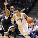 Duke guard Tyus Jones (5) drives against Connecticut guard Ryan Boatright during the second half of an NCAA college basketball game, Thursday, Dec. 18, 2014, in East Rutherford, N.J. Duke won 66-56. (AP Photo/Julio Cortez)
