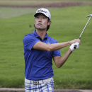 Kevin Na watches his shot after taking a penalty drop when he lost his ball in a rain-swollen drainage culvert adjacent to the 18th fairway during the second round of the Colonial golf tournament, Friday, May 22, 2015, in Fort Worth, Texas. Na recovered for par on the hole. (AP Photo/LM Otero)