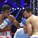 Nicaraguan challenger Roman Gonzalez, left, sends his left to Japanese champion Akira Yaegashi in the fourth round of their WBC flyweight boxing title match in Tokyo, Friday, Sept. 5, 2014. Gonzalez won the title after defeating Yaegashi by a technical knockout in the 10th round. (AP Photo/Toru Takahashi)